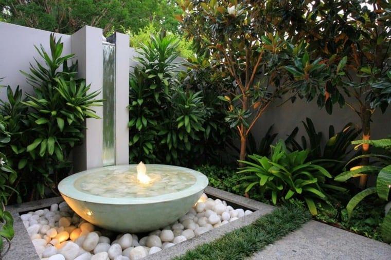 fuente de marmol con piedras blancas de río para decorar jardín minimalista